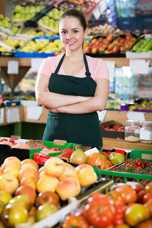 Smiling female grocery worker in apron near shelves of fruits and vegetables