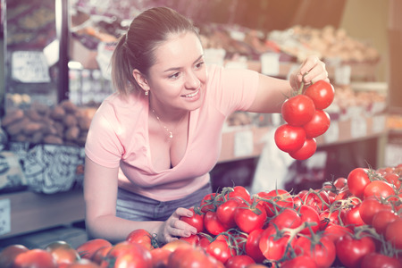 Young female looking for fresh tomatoes in vegetable store Stock Photo