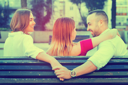 Image of the love triangle between young smiling  people outdoor