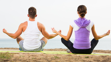 Positive cross-legged guy and girl training yoga poses on beach Stock Photo