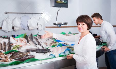Female customer buying fish and chilled seafood in shop