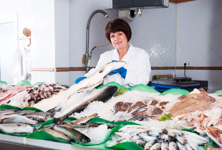 Friendly senior woman posing near display with cooled fish and seafood