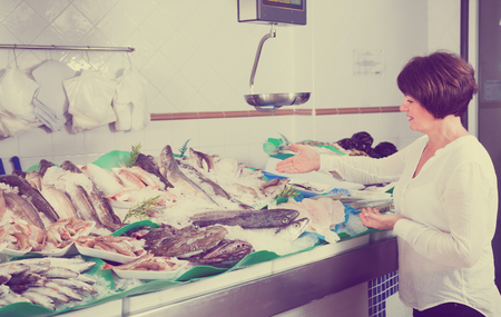 Ordinary female customer buying fish and chilled seafood in shop 写真素材