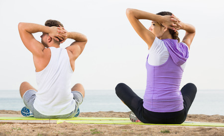 Cross-legged young  couple practice yoga on beach in morning
