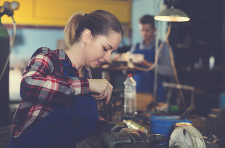 Portrait of female who is repairing drill on her workplace in workshop. Stockfoto
