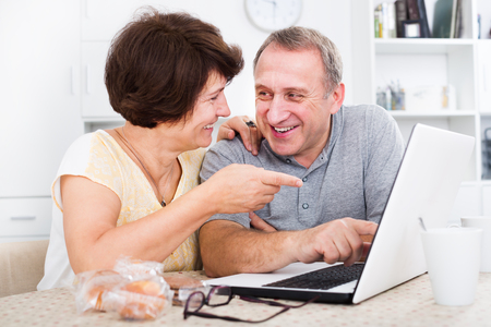 Laughing mature man and woman discussing while looking at the laptop together at a home. Focus on man