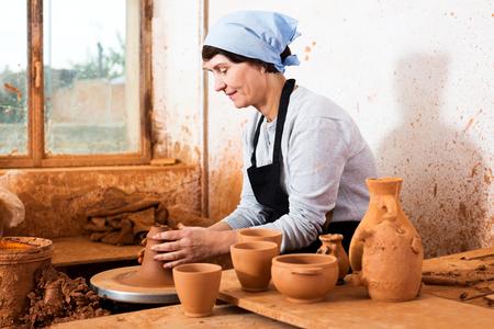 Sonriendo anciano maestro entre la cerámica en el taller
