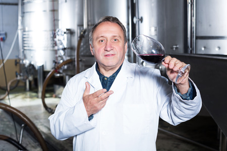 Elderly wine maker controls quality of wine at winery