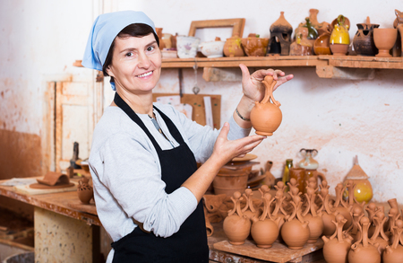 Happy elderly brunette female  potter working at workshop Stock Photo