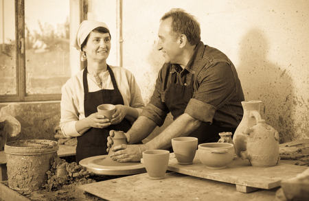 Elderly positive couple among the pottery at the workshop