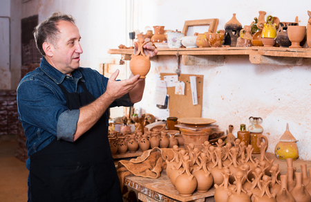 Glad adult master among the pottery at the workshop