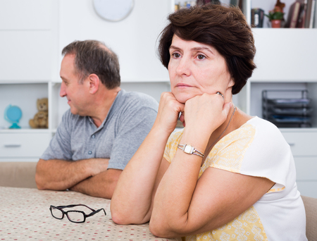 Portrait of worried mature woman having issues with her husband at home