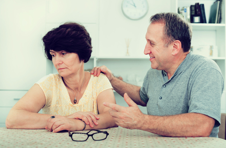 Sad mature woman experiencing family problems with partner indoors. Focus on both persons Фото со стока