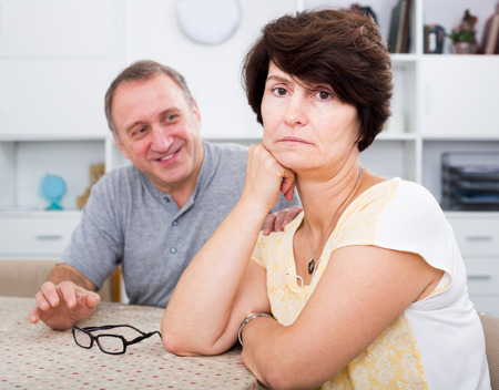 Portrait of unhappy mature woman having issues with her husband at home