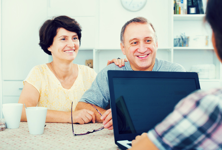 Attentive positive mature couple looking at woman showing documents at the her laptop indoors. Focus on mature man