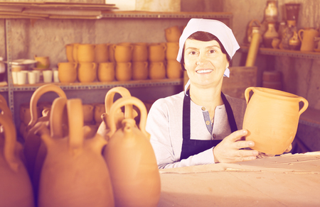 Elderly female  potter working at workshop
