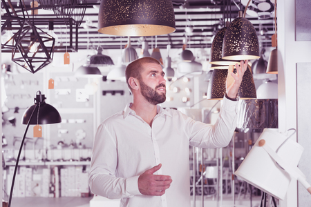 Portrait of man choosing  suspension lamp in furniture showroom