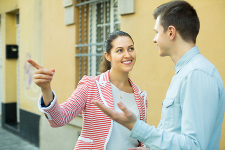 Traveller asking happy young woman to show him direction