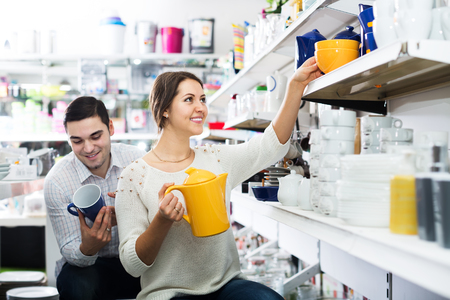 Happy couple buying ceramic tableware in shop cookware Stock Photo