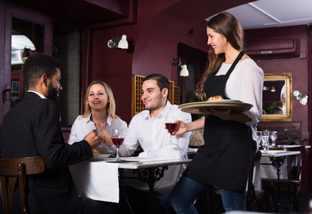Portrait of chatting 25s adults in restaurant and cheerful waitress