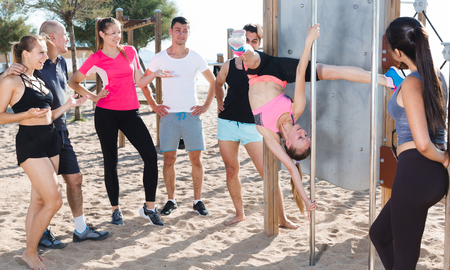 Sporty girl performing pole exercises causing admiration of people watching her Stok Fotoğraf
