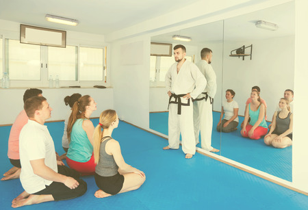 Young coach will give instructions to his students before training on karate in the gym