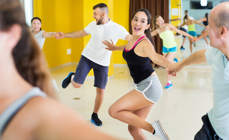 Young happy sporty girls and men learning swing steps  Stock Photo