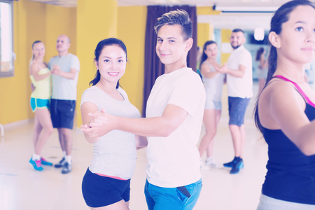 Group of young active men and women dancing bachata in dance studio  Stock Photo