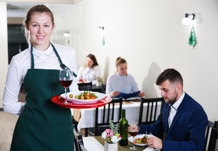 Portrait of welcoming female waiter who is standing in restaurante indoor. Banco de Imagens