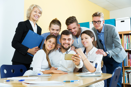 Group of students and female professor taking selfie in auditorium