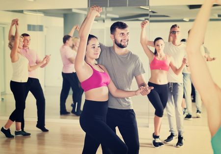Positive couples enjoying of partner dance and smiling indoor Banque d'images