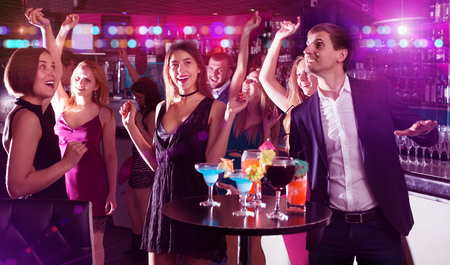 Young students dancing on university party with cocktails in the club  Stock Photo