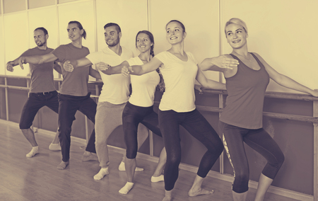 Group of smiling american men and women practicing at the ballet barre 版權商用圖片