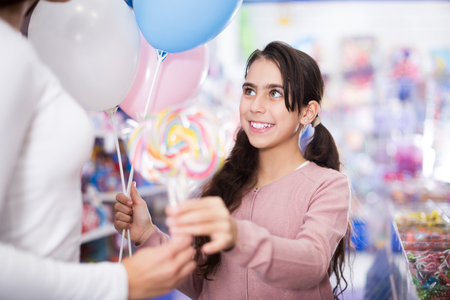 Smiling small girl with balloons receives lollipop in the toys shop