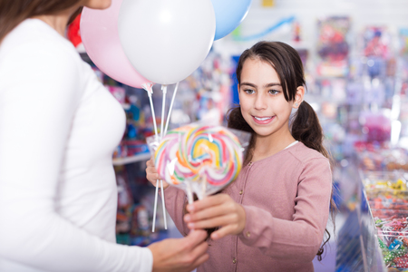 Girl daughter with balloons holding lollipop in candy store Stock Photo