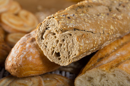 Closeup of cut wholegrain baguette with various bakery products on wicker mat