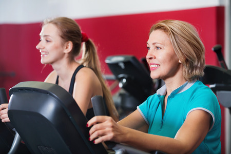 Smiling satisfied elderly and young women working out in gym for female