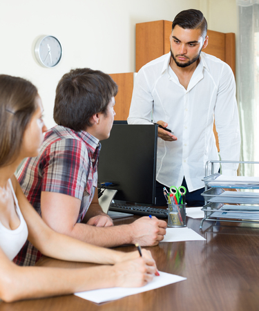 Bank employee at the office trying hard to make young couple pay back debts Stock Photo