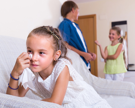 Upset crying little girl is jealous sister of stepbrother indoors