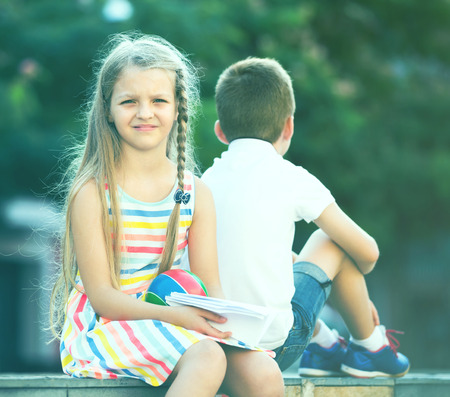 Portrait of bored little girl sitting back to friend outdoors in park
