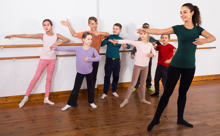 Group of positive american children practicing at the ballet barre Banque d'images