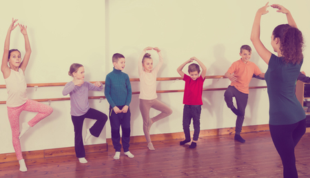 industrious boys and girls primary school age rehearsing ballet dance in studio Banque d'images