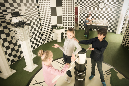 Captured children with interest play in quest room in chess style Imagens