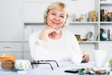Close-up portrait of a mature healthy woman sitting at the table at home