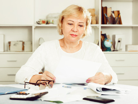 Mature woman at home is engaged in home accounting Foto de archivo