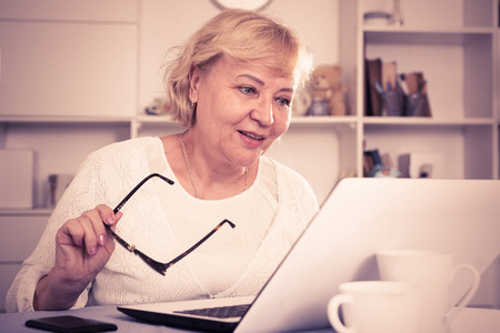 Mature woman sitting at home in front of laptop at table Stock Photo