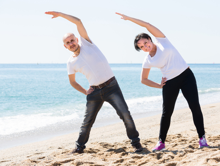 positive american mature man and woman exercising together on the beach Stock Photo