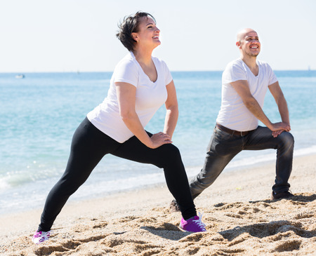 portrait of a happy smiling adult couple training together by the sea