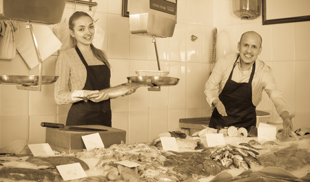 Fresh fish and seafood store with two joyful smiling sellers in aprons at the counter