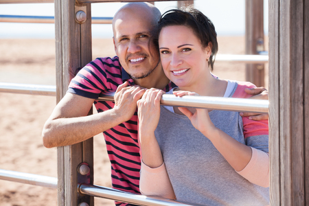 Happy man and woman standing together close to wall bars and smiling